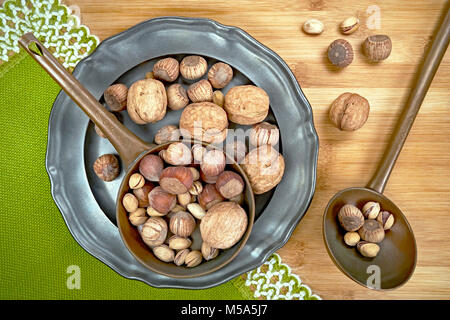 Nuts of various kinds on a metal plate, from above on a wooden board - Stock Photo