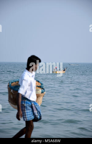 Fisher men setting up his nets in sea & a busy groundnut seller passing by on the beach. - Stock Photo