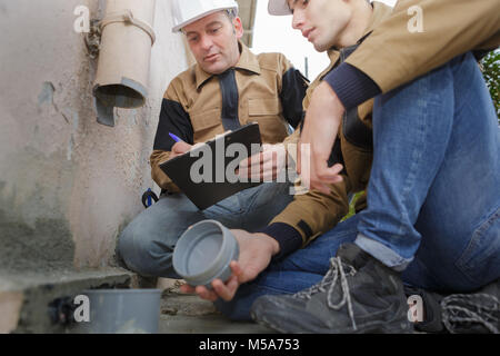 two workers working on gutter - Stock Photo