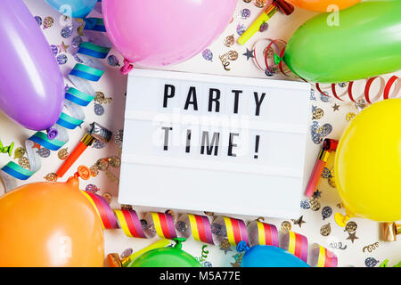 Party celebration background with party time message on a lightbox - Stock Photo