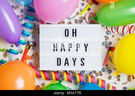 Party celebration background with oh happy days message on a lightbox - Stock Photo