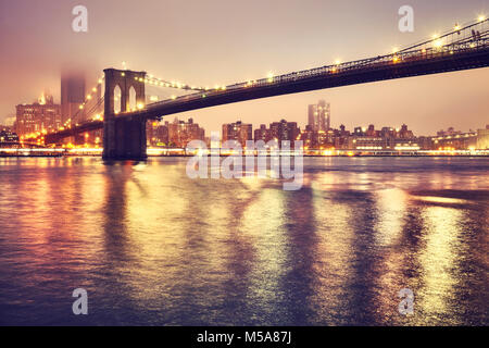 Brooklyn Bridge and the Manhattan on a foggy night, color toned picture, New York City, USA. - Stock Photo