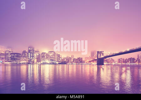 Color toned picture of the Manhattan on a foggy night, New York City, USA. - Stock Photo