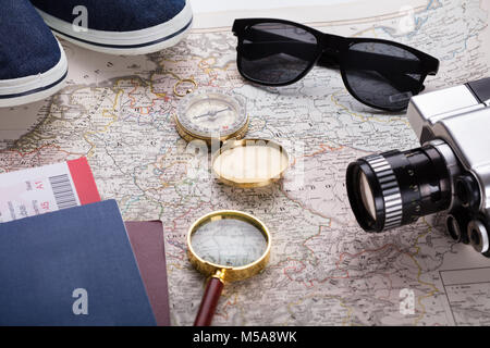 High Angle View Of Boarding Pass Ticket, Passport And Camera On Map - Stock Photo