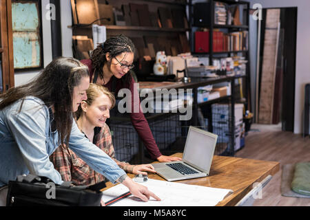 Three women gathered around table in office area of a metal workshop. - Stock Photo