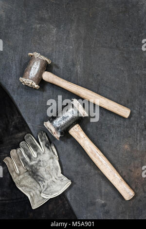 High angle close up of two hammers and pair of leather safety gloves in a metal workshop. - Stock Photo