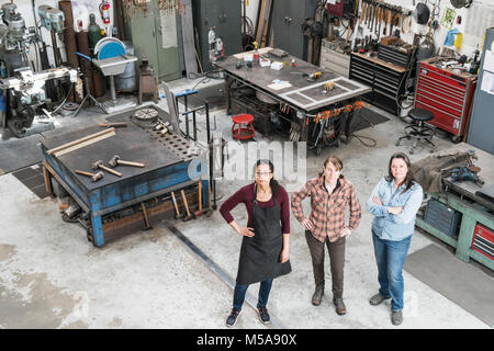 High angle view of three women standing in metal workshop, looking at camera. - Stock Photo