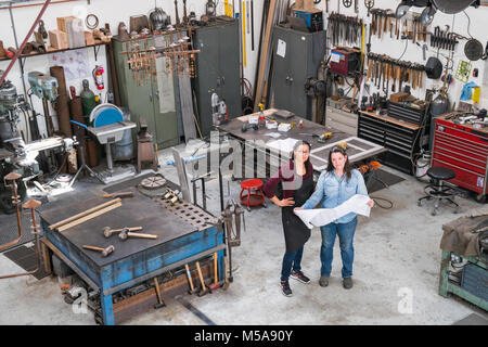 High angle view of two women standing in metal workshop, holding technical blueprint. - Stock Photo