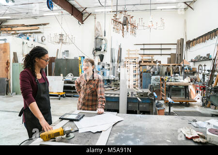 Two women standing at workbench in metal workshop. - Stock Photo