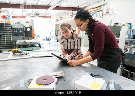 Two women standing at workbench in metal workshop, looking at digital tablet. - Stock Photo
