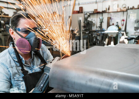 Woman wearing safety glasses and dust mask standing in metal workshop, using power grinder, sparks flying. - Stock Photo