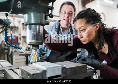 Two women wearing safety glasses standing in a metal workshop, working on metal drilling machine. - Stock Photo