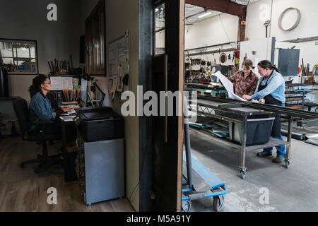 Two women at a desk in office area of a metal workshop, woman standing at mobile workbench. - Stock Photo