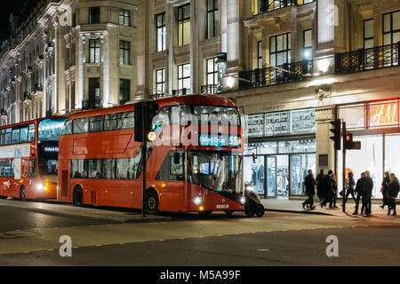 New red double decker bus waiting on traffic light on Regent Street, a major shopping street in the West End of - Stock Photo