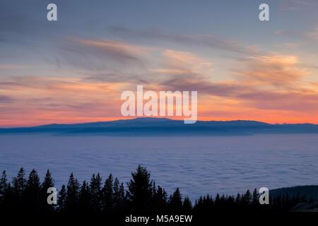 View from mountain Schoeckl in Styria over low stratus to mountain ranges Koralpe and Pack to sunset - Stock Photo