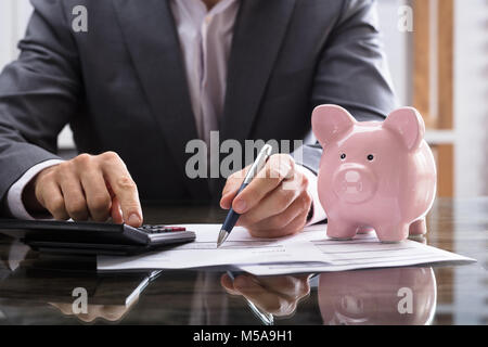 Businessperson Calculating Bill With Pink Piggybank On Desk - Stock Photo