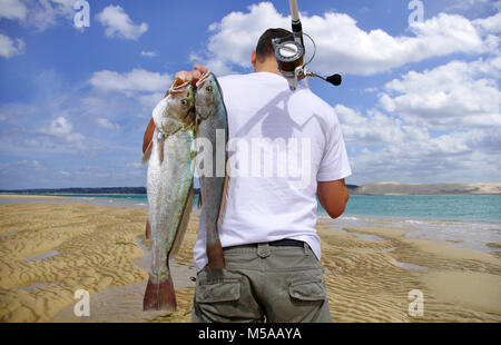 A surf fisherman with two big saltwater fish on a paradise beach - Stock Photo
