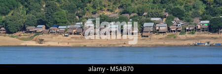 A detailed panoramic of a small village at the Irrawaddy River in Myanmar Burma with huts along the river bank - Stock Photo