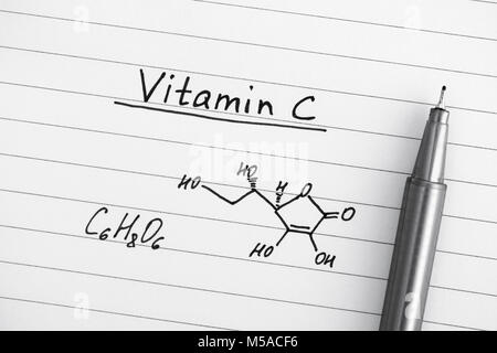 Chemical formula of Vitamin C with pen. Close-up.