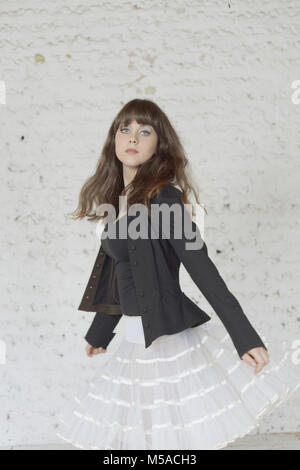 A beautiful girl with long brown hair dances in front of a white painted wall- her hair moves, she is unsmiling - Stock Photo