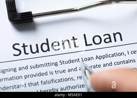Elevated View Of Person's Finger With Pen Over Student Loan Form - Stock Photo
