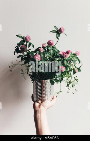 hand holding clover bouquet with pink flowers in metallic cane. wildflowers in rustic rural home. country slow living - Stock Photo