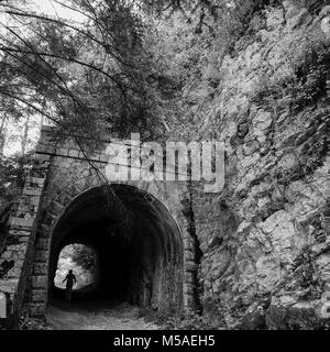 Walking through a tunnel on the footpath to Mount Revard, Savoy, France - Stock Photo