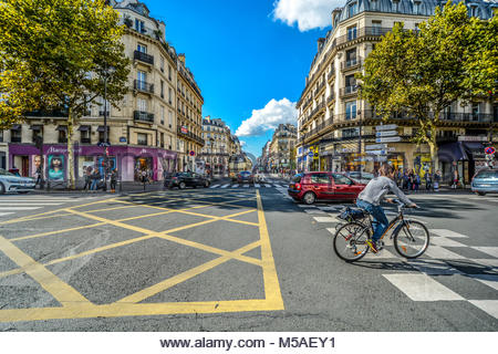 A bicyclist rides through an intersection along the Rue du Rivoli with cars and shops on a sunny summer day in Paris - Stock Photo