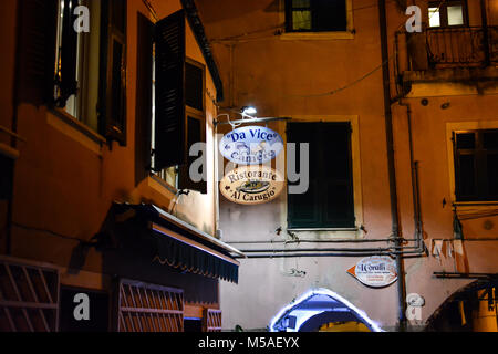 Late night in Monterosso Al Mare, Cinque Terre Italy with a colorful sign of violet and peach advertising an Italian - Stock Photo
