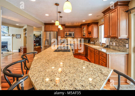 Spacious upscale kitchen in a luxury home with large granite slab center island with bar stools, granite counters - Stock Photo