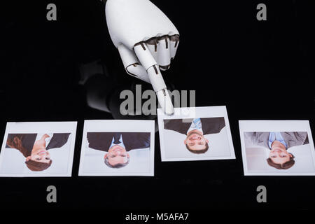 Close-up Of A Robot's Hand Selecting Candidate Photograph - Stock Photo