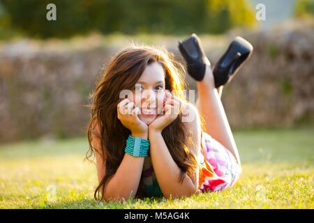 Good girl lying on meadow sunshine highlights on long brunette hair enjoying nature lazy afternoon giggling giggle - Stock Photo