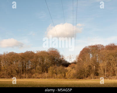 view of large electrical wire metal pylon outside in nature field wires overhead; essex; england; uk - Stock Photo