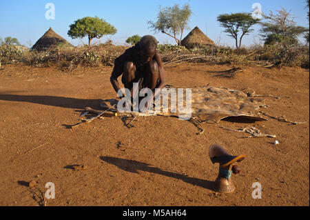 A man is tanning leather ( Ethiopia). He belongs to the Hamer tribe. - Stock Photo