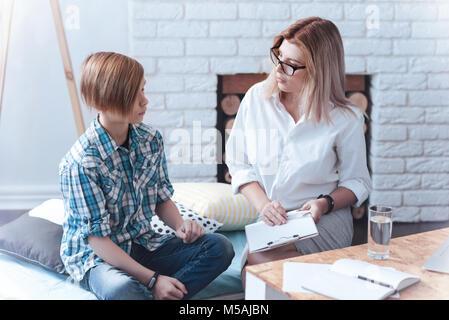 Teenage boy attending professional psychotherapist - Stock Photo