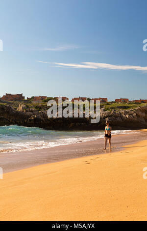 woman walking through the sand of a lonely and beautiful beach - Stock Photo