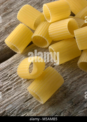 Traditional dried  Italaian Mezze Maniche Rigate pasta close up in a rustic setting on wood - Stock Photo