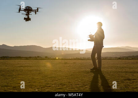 Drone pilot after take off with a cinema drone - Stock Photo