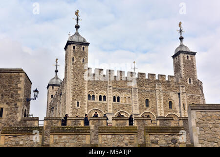 the tower of london wall facing the river thames. visitors and tourists on the walls and battlements of the tower - Stock Photo
