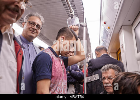 Tehran, Iran - April 29, 2017: Iranian men of different ages ride the subway, one of them listens to music on headphones, - Stock Photo