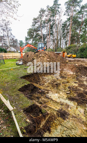 Large orange heavy plant mechanical digger parked on an earth mound after digging excavations for foundations of - Stock Photo