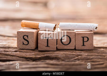 Close-up Of A Cigarette And Wooden Blocks Showing Stop Word On Desk - Stock Photo