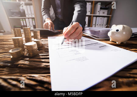 Close-up Of A Businessperson's Hand Signing Document With Stacked Golden Coins On Wooden Desk - Stock Photo