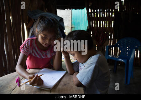 Lizeth Haup Pool shares her knowledge of Mayan mathematics with her little brother Gehu Hapu Pool at their home - Stock Photo