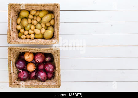 Two wicker baskets with fresh potatoes and onions side by side on a white wood background with copy space viewed - Stock Photo