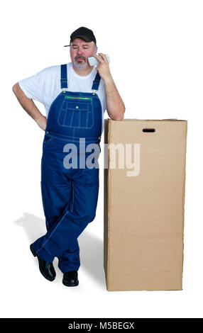 Home installer getting instructions on his mobile phone as he stands leaning on a large brown cardboard box with - Stock Photo