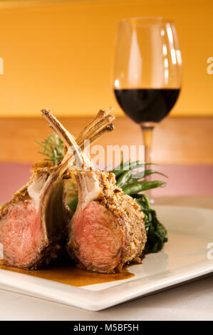 Rack of lamb chops ribs on bone upright plated, green vegetables, red wine in restaurant setting, vertical, cover, - Stock Photo
