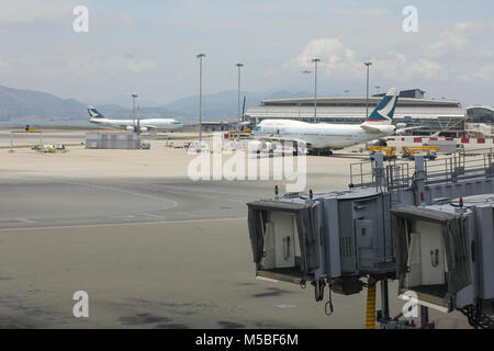 Two planes of the Cathay pacific company in the hub of Chek Lap kok airport in Hong Kong. - Stock Photo