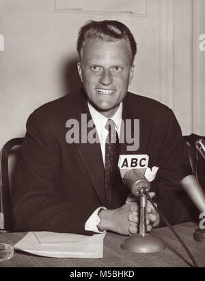 American evangelist Billy Graham (1918-2018) sitting at desk with media microphones on September 20, 1958. - Stock Photo
