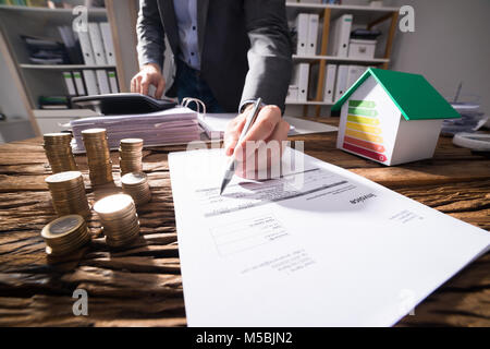 Businessperson Calculating Bill With Coins And House Model Showing Energy Efficiency Rate On Desk - Stock Photo